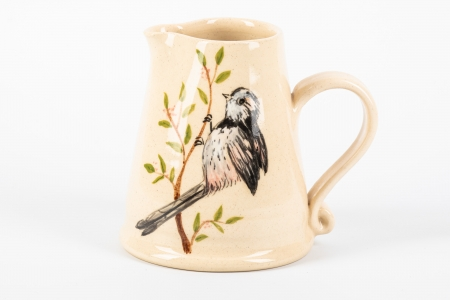 A photo of a small white jug with a long tailed tit bird on the side