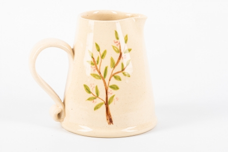 A photo of a small white jug with a branch with flowers on the side