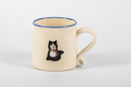 A photo of a white childs ceramic mug with a cat on the side