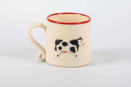 A photo of a white childs ceramic mug with a cow on the side