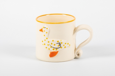 A photo of a white childs ceramic mug with a spotty duck on the side