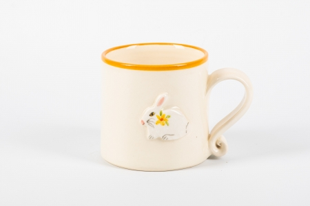 A photo of a white childs ceramic mug with a rabbit on the side