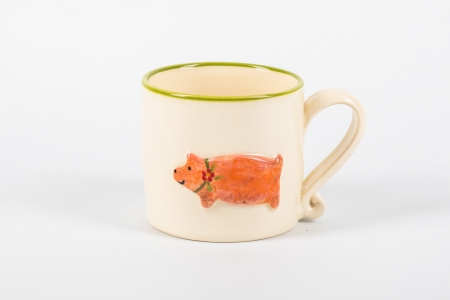A photo of a white childs ceramic mug with a pig on the side