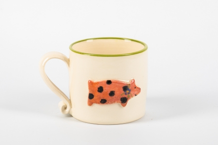 A photo of a white childs ceramic mug with a spotty pig on the side