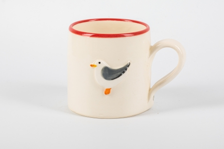 A photo of a white childs ceramic mug with a seagul on the side