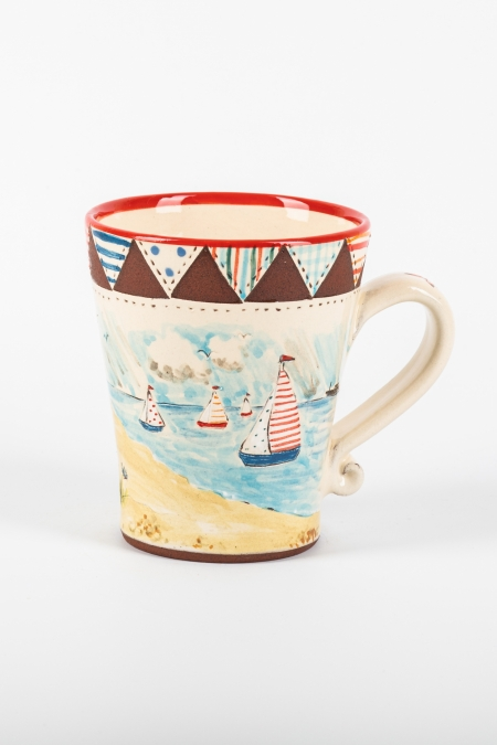 A photo of a mug with patchwork and seaside decoration
