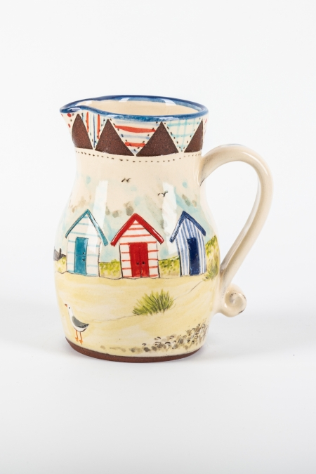 A photo of a jug with patchwork and seaside decoration