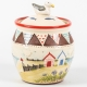 A photo of a storage jar with patchwork and seaside decoration