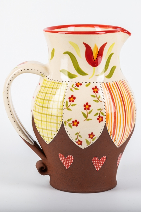 A photo of a jug with patchwork and floral decoration