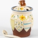 A photo of a storage jar with patchwork decoration and a rabbit for the handle