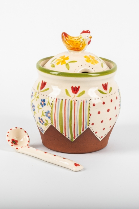 A photo of a storage jar with patchwork decoration and a chicken for the handle