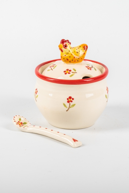 A photo of a storage and spoon jar with a chicken for the handle
