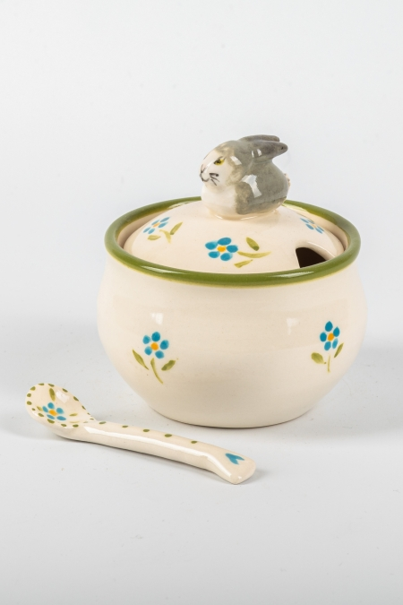 A photo of a storage jar and spoon with a rabbit for the handle