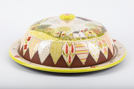 A photo of a cheese dish with patchwork effect and garden scenery decoration.