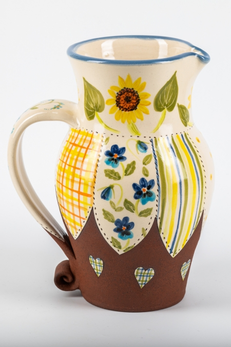 A photo of a jug with sunflower design with patchwork effect on both sides