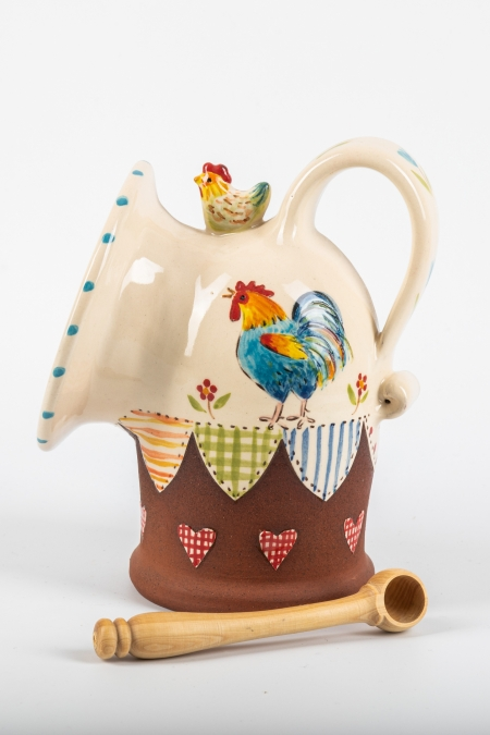 A photo of a salt pig with a blue chicken design with patchwork and hearts effect and a chicken on top.