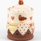 A photo of a ceramic garlic pot with floral patchwork decoration and chickens and hearts on the side and a chicken on top