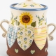 A photo of a ceramic storage jar with sunflowers on the side and patchwork effect decoration