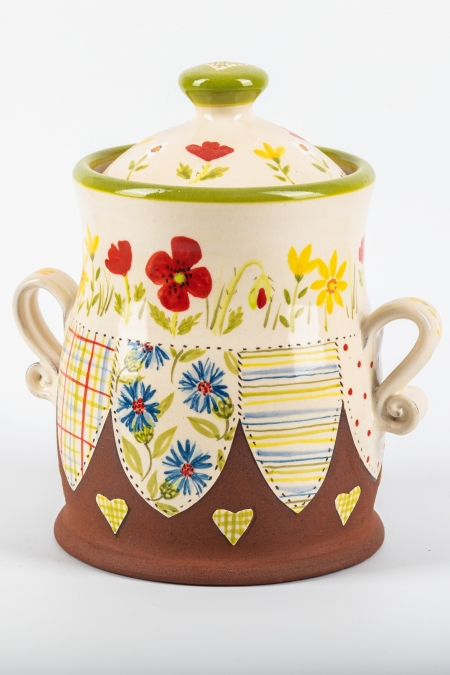 A photo of a ceramic storage jar with a poppy and meadow flowers on the side and patchwork effect decoration