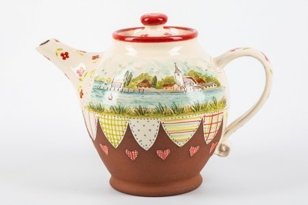 A photo of a ceramic teapot with seascape painting on the side and patchwork effect decoration