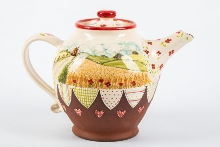 A photo of a ceramic teapot with landscape painting on the side and patchwork effect decoration