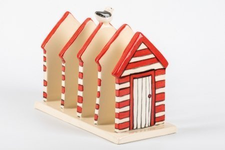 A photo of a hand made ceramic toast rack decorated and shaped from 5 house shapes