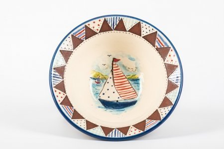 A photo of a hand made ceramic bowl with patchwork effect around the rim and a boat scene hand painted in the centre