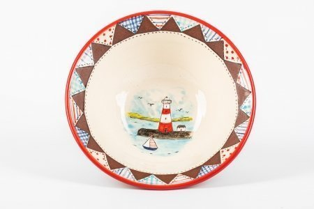 A photo of a hand made ceramic bowl with patchwork effect around the rim and a lighthouse scene hand-painted in the centre