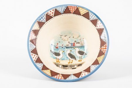 A photo of a hand made ceramic bowl with patchwork effect around the rim and a seagull scene hand-painted in the centre in the centre