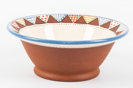 A photo of a hand made teracotta ceramic patchwork effect bowl from the side