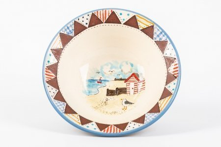 A photo of a hand made ceramic bowl with patchwork effect around the rim and a beach scene hand-paintedin the centre