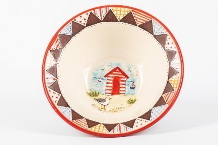 A photo of a hand made ceramic bowl with patchwork effect around the rim and a beach-hut design painted in the centre