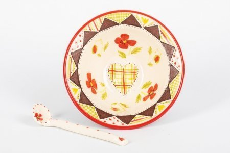 A photo of a hand made teracotta ceramic patchwork effect bowl with a floral design in the centre and a ceramic spoon next to it