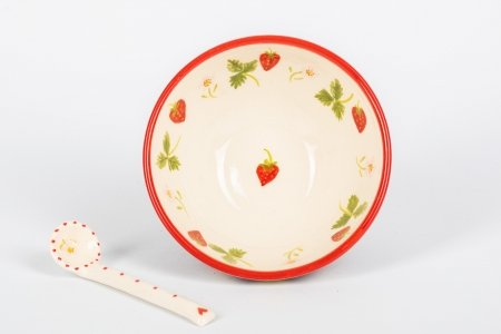 A photo of a hand made teracotta ceramic with a red rim, a floral design in the centre and a ceramic spoon next to it