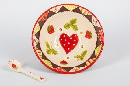 A photo of a hand made teracotta ceramic patchwork effect bowl with a strawberry design in the centre and a ceramic spoon next to it
