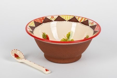 A photo of a hand made teracotta ceramic patchwork effect bowl from the side with a ceramic spoon next to it