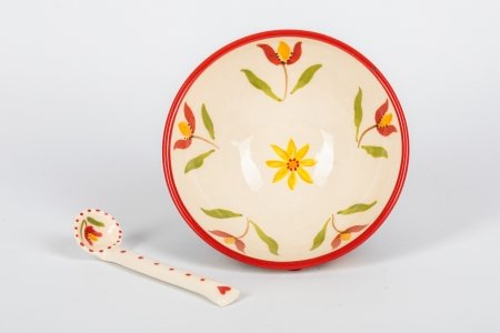 A photo of a hand made teracotta ceramic patchwork effect bowl with a tulip design in the centre and a ceramic spoon next to it