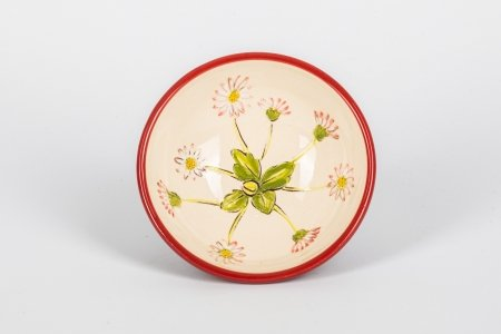 A photo of a hand made ceramic bowl taken from the top with a red rim and floral design in the centre