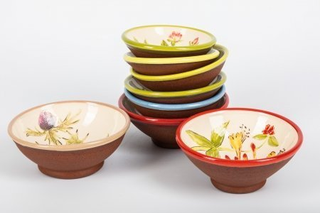 A photo of a selection of hand-made ceramic bowls with different bright coloured rims rim, some are piled up, in a stack.