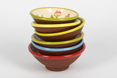 A photo of a stacked selection of handmade ceramic bowls with different bright coloured rims