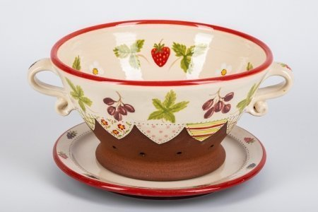 A photo of a hand made teracotta ceramic patchwork effect Colander and plate decorated with strawberries, berries and flowers
