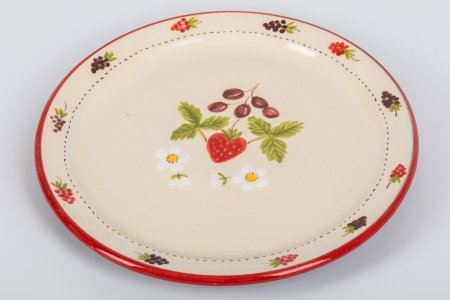A photo of a hand made terracotta ceramic plate decorated with strawberries, berries and flowers