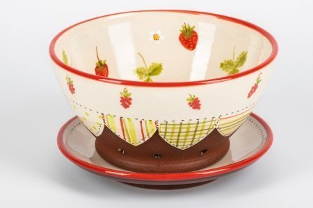 A photo of a handmade ceramic patchwork effect colander and plate decorated with strawberries