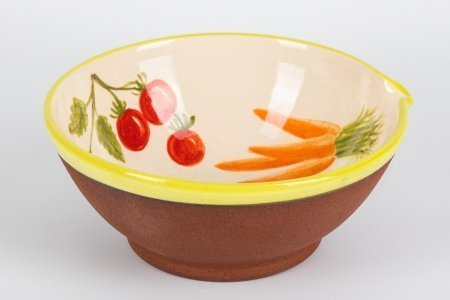 A photo of a handmade ceramic bowl decorated with mixed vegetables on the inside and plain matt teracotta clay on the outside of the bowl.