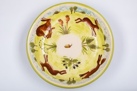A photo of a white handmade ceramic bowl taken from the top, decorated with four running hares and foxes