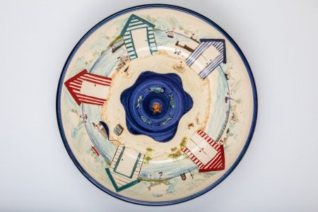 A photo of a white handmade ceramic bowl taken from the top, decorated with a seascape with beach huts and fish seagrass and boats.