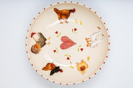 A photo of a white handmade ceramic bowl hand decorated with a variety of chickens and ducks all around the centre and a red gingham heart with tulips in the centre.