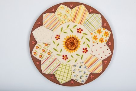 A photo of a patchwork effect platter with plain matt terracotta on the edges and glossy bright colour floral design on the platter centre.