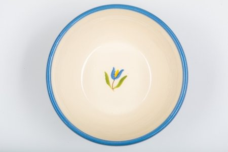 A photo of a white ceramic bowl, taken from the top, hand decorated with a blue rim and a red tulip in the centre