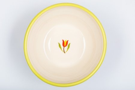 A photo of a white ceramic bowl, taken from the top, hand decorated with a green rim and a red tulip in the centre
